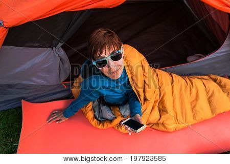 Girl With A Phone In A Sleeping Bag.