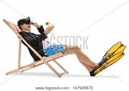 Businessman with a cocktail sitting in a deck chair and using a VR headset isolated on white background