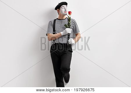 Mime artist smelling a flower and leaning against a wall
