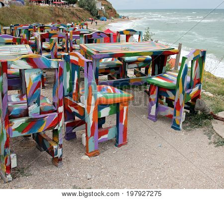 Colored chairs and table at a beach retro cafe