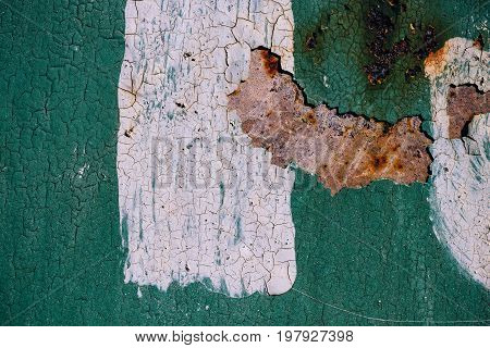 Rusty metal surface with cracked green paint abstract rusty metal texture green rusty metal background with a strip of white paint in the center decay steel decay