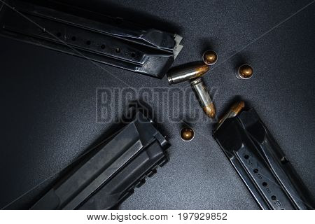 9 mm Pistol, bullets and magazine on black background. Gun isolated