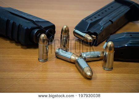 9 mm Pistol, bullets and magazine on wooden background. Gun isolated