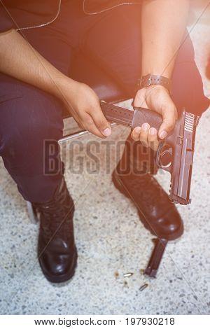Man or gangster loading bullets handgun, focus on gun.