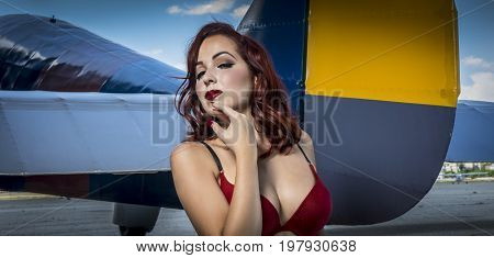 Lady Beautiful redhead girl dressed in style pinup of the second world war, next to a military plane