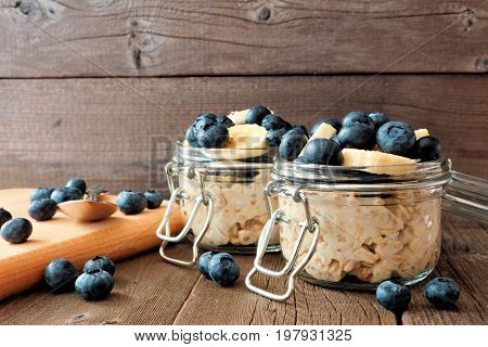 Overnight Oats With Fresh Blueberries And Bananas In A Snap Lid Jar On A Rustic Wood Background