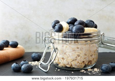Jar Of Overnight Oats With Fresh Blueberries And Bananas, Scene With White And Black Stone Backgroun