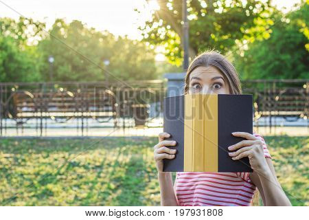 Young cute girl covers her face with a book. Surprised and shocked woman. Emotional girl holding a book in her hands.