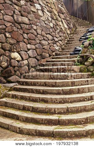 Beautiful winding stone steps spiraling up and around a curve alongside a stone wall.