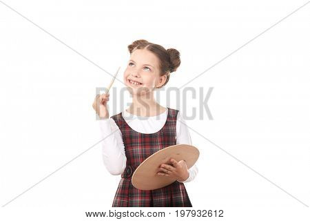 Portrait of cute girl in school uniform painting against white background