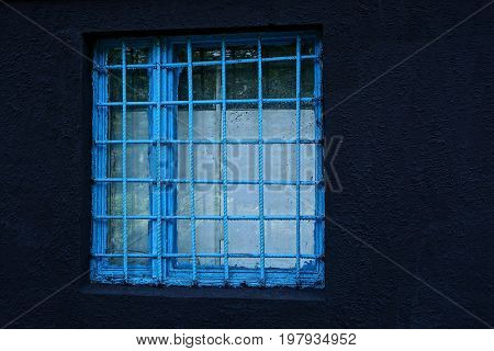 A square window behind a blue lattice on a black concrete wall