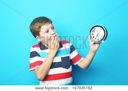 Portrait of emotional boy with round clock on blue background