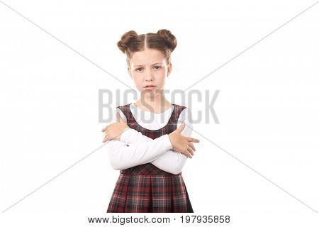 Portrait of offended girl in school uniform standing cross-armed against white background