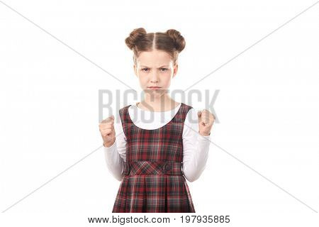 Portrait of displeased girl in school uniform ready to fight against white background