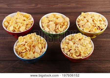 Cornflakes in bowls on the wooden table