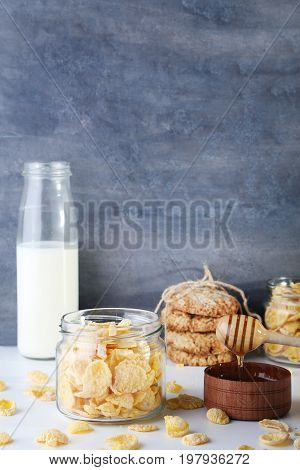 Cornflakes, Bottle Of Milk And Bowl Of Honey On Wooden Table