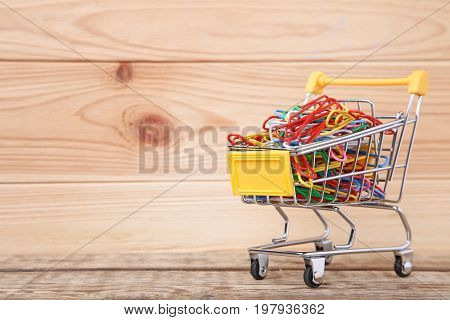 Shopping Cart With Paperclips On Wooden Table