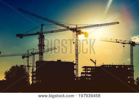 Silhouette Of Tower Cranes On Industrial Construction Site. New District Development And Skyscraper