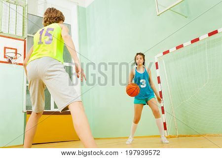 Low angle view of teenage girl dribbling the ball during the basketball match in school gymnasium