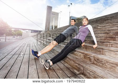 Sporty young couple holding correct position of reverse plank, exercising together outdoors on city stairs