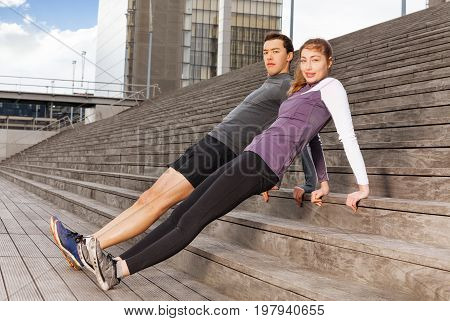Portrait of active young people doing the reverse plank exercises outdoor on city stairs