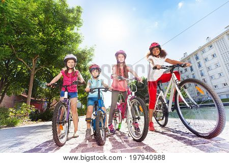 Full-length portrait of happy preteen girls and boy standing with their bicycles in line in summer city