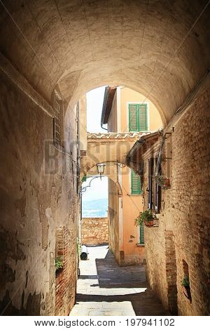 Medieval arched street in the old town of Montepulciano, Italy. Picturesque ancient narrow alley with archway in the old town