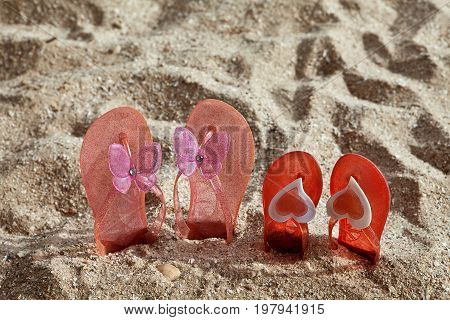 Two pairs of beach Slippers stuck in the sand
