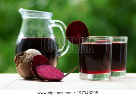 Two glasses of beet juice and a jug. Next beet and slices.