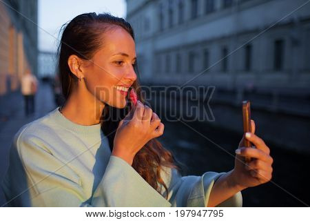 Attractive young girl paints lips in the light of the setting sun. deals lipstick on the lips.