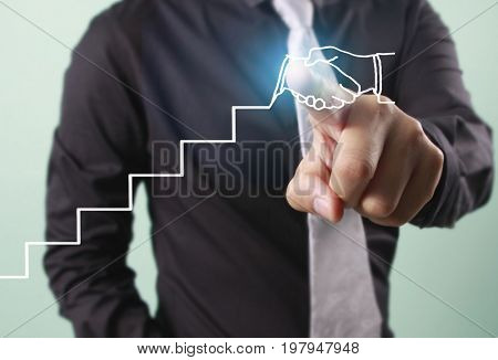 Businessman touching graphic of business connection concept and successful partnership network with handshake illustration line chart on visual screen, green background, financial concept