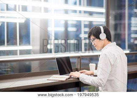 Young Asian man businessman dressed in casual style listening to music while working with laptop computer. Digital nomad in co working space freelance lifestyle with work life balance concept.