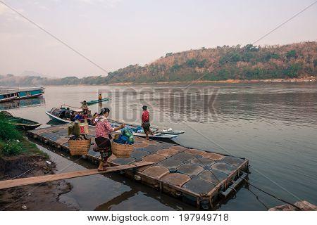 LUANG PRABANG LAOS - MARCH 12 2017: Local people bring food in a basket to the boat in Mekong's River in Luang Prabang Laos.