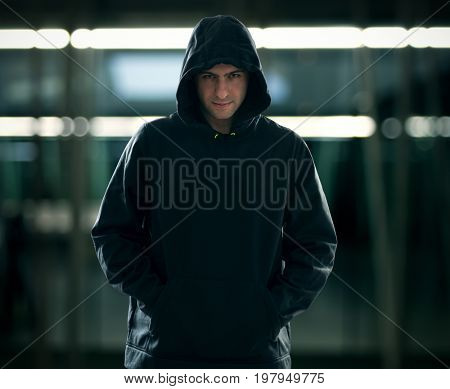 Portrait of a man wearing a hoodie in a dark environment