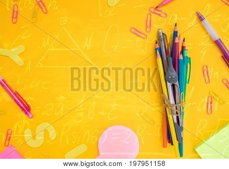 back to school or office styed frame with multicolored school supplies on yellow with math formulas