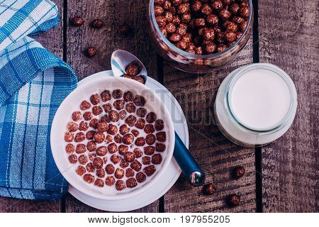 Healthy breakfast concept. Cereal chocolate balls with milk on wooden table background. Top view