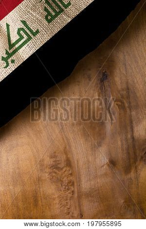 The national flag of Iraq on a wooden background.