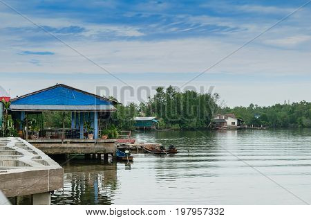 Houses along the river with long tail boats in the middle of Thailand.