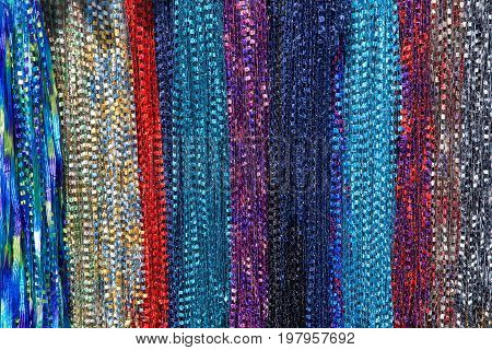 Background fabric strings creating scarfs multiple colored scarves hanging in rows. yellow red blue purple maroon aqua
