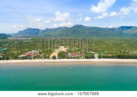 Bird eye view of beautiful turquoise seawater at the beach and green mountains in background - Southern Thailand