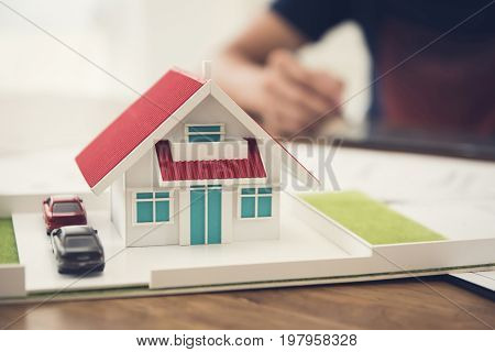Car and house model on the table with blur working people in background - architecture and real estate service concept
