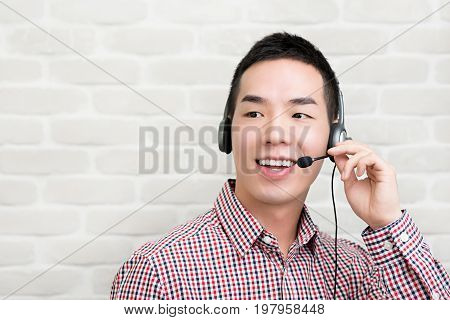 Casual Asian businessman wearing microphone headset as a telemarketing customer service agent call center job concept