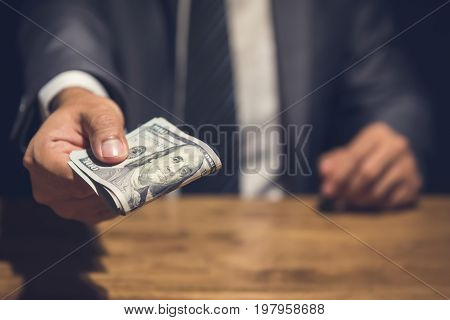 Dishonest businessman secretly giving away money in the dark - bribery scam and venality concepts
