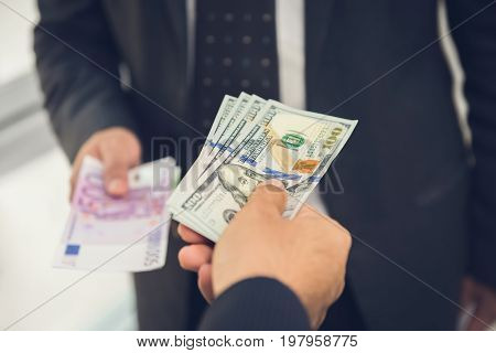 Businessman exchanging money US dollar bills with Euro currency