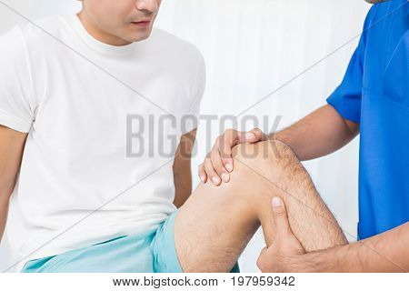 Therapist treating injured knee of male patient in hospital - physical therapy concept