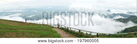 Panorama of woman looking at view of mountain landscape with waves of fog and cloudy sky. Phu Tub Berg Phetchabun province Thailand
