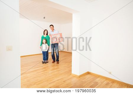 family in an empty apartment, holding 'for sale' sign