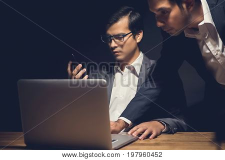Businessmen using laptop computer working late at night in dark room - workaholic and hacker concept