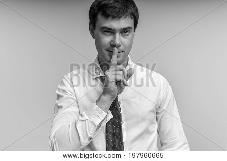 Attractive man with finger on lips and red lipstick on shirt collar making silence gesture - infidelity concept