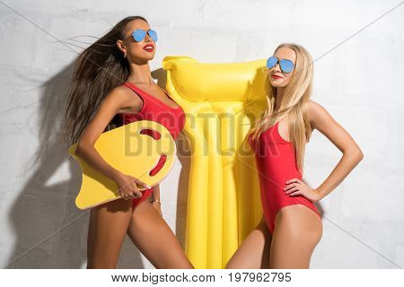 Two sexy girls wearing sunglasses, red swimsuit and summer hat posing in studio near brick white wall holding swimming air mattress